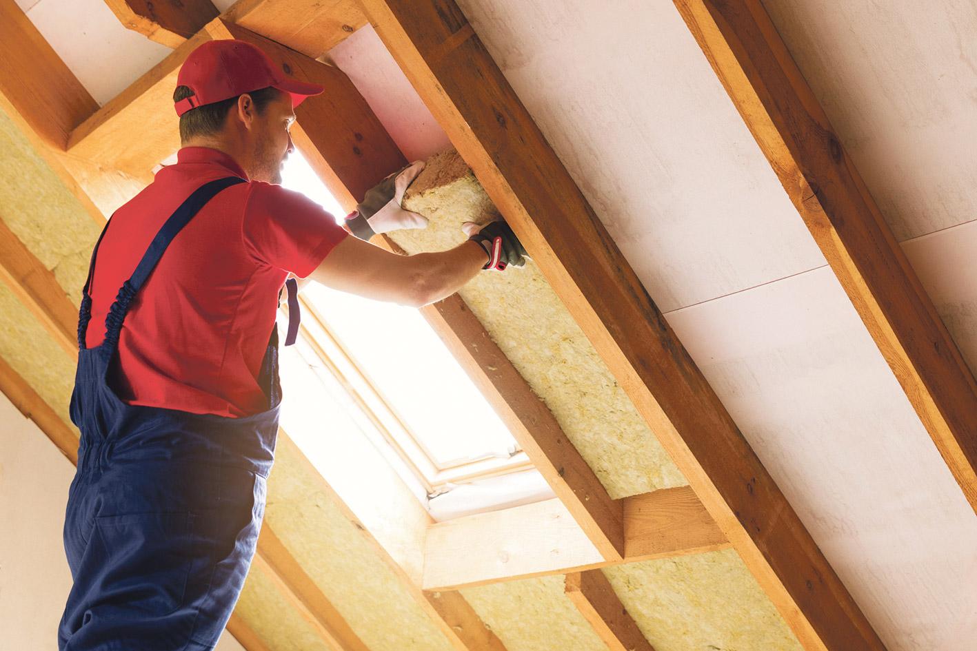 Person, die eine Gebäudewand dämmt, um Energie zu sparen.