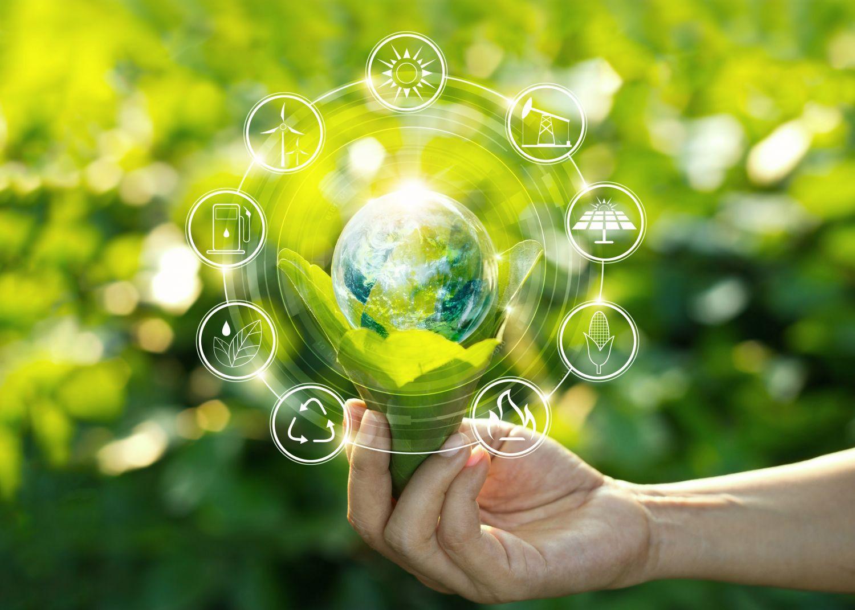 Hand hält Weltkugel fest, Symbole drum herum sollen Wirtschaftssektoren aufzeigen. Thema: Regnerative Energien