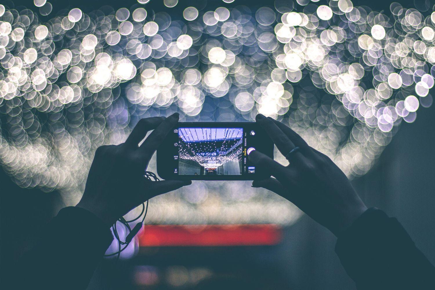 Jemand richtet sein Smartphone auf Lichterketten, um sie zu fotografieren