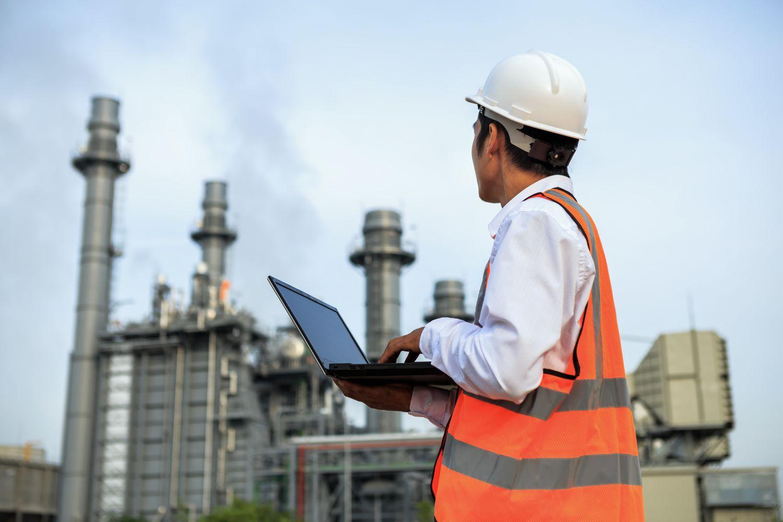 Arbeiter mit Laptop vor Kraftwerk.