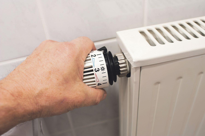 Ein Mensch dreht am Thermostat einer Heizung. Wer Geld sparen will, sollte in Erwägung ziehen, seine Heizung zu modernisieren