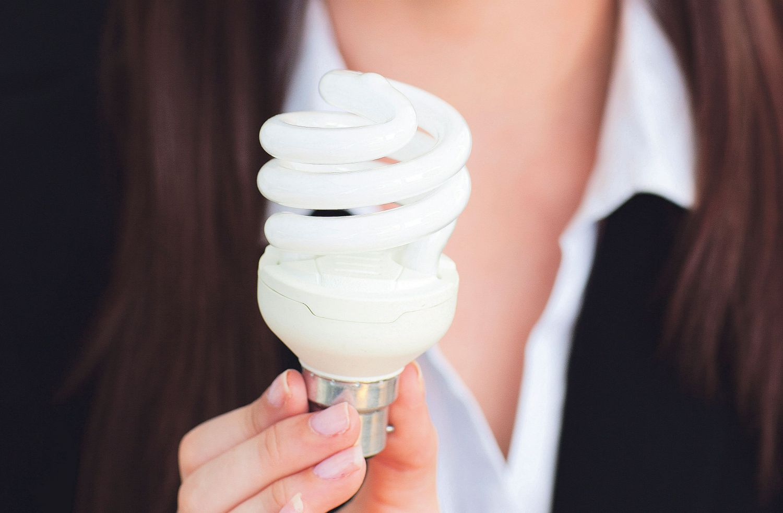 Eine Frau hält eine Energiesparlampe in ihrer Hand. Wenn Mitarbeiter Energie sparen, bringt das dem Unternehmen nicht nur finanzielle Vorteile