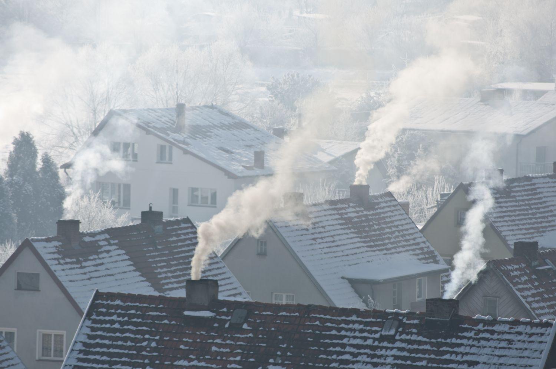 Rauchende Schornsteine auf Häuserdächern im Winter. Nach der Wärmewende sollte dieses Bild eine Seltenheit werden