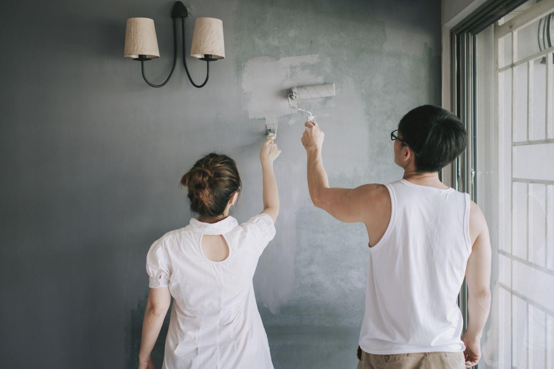 Paar streicht eine Wand im zuhause
