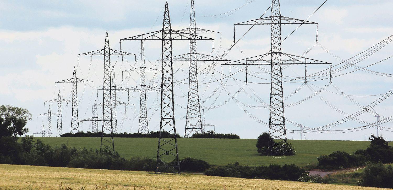 Hochspannungsmasten zwischen Feldern. Das Stromnetz führt durch alle Ecken Deutschlands