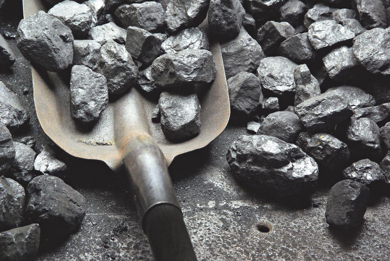 Eine Metallschippe liegt im Kohlehaufen. Kohle und Klimaschutz sind ein Streitthema