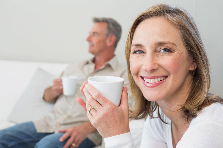 Ein Paar sitzt mit Getränken auf der Couch. Darum, welche Heiztechnik die richtige ist, macht es sich gerade Gedanken