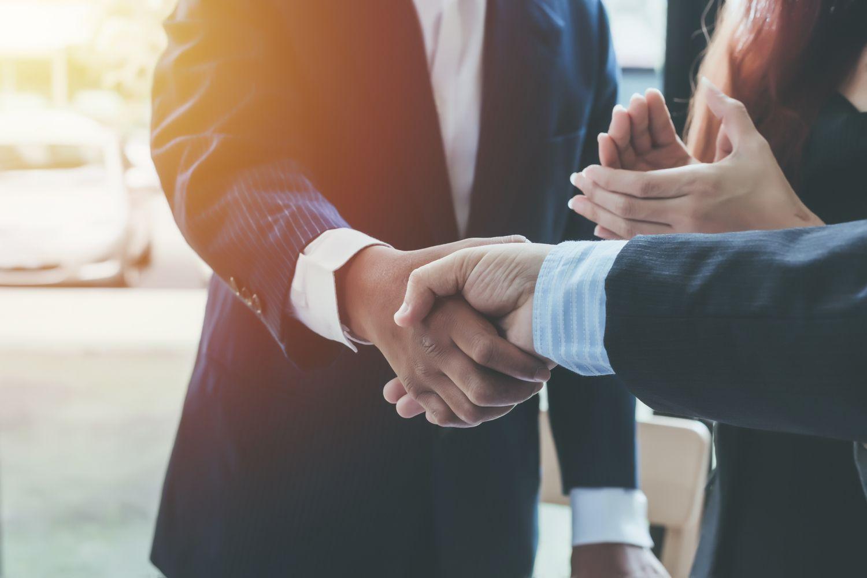 Geschäftspartner schütteln sich unter Applaus die Hände