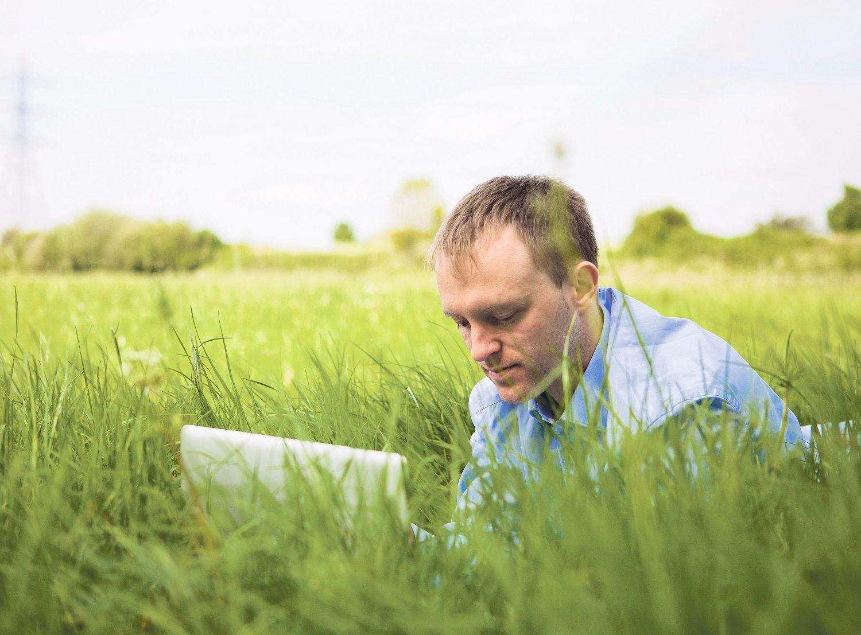 Ein Mann sitzt mit Laptop im Gras.
