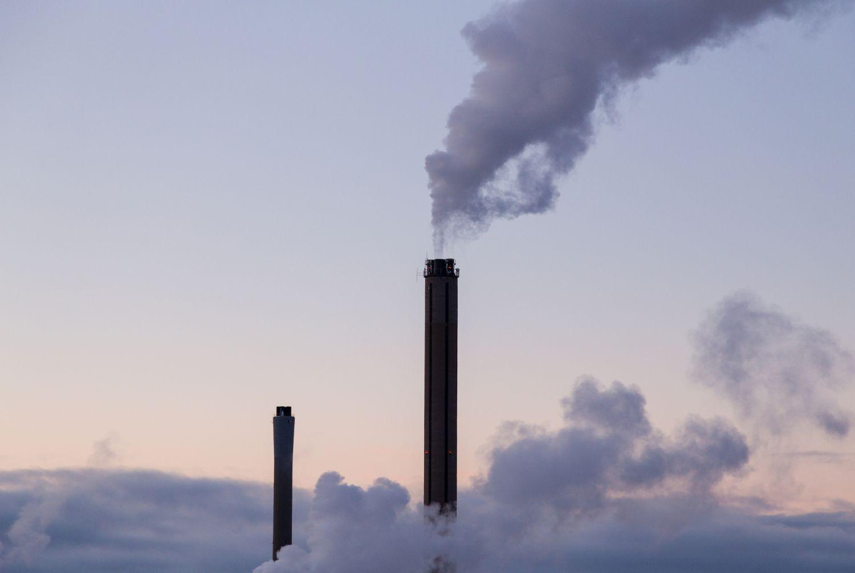 Qualmende Schornsteine einer Fabrik. Thema: Industrie will und muss Emissionen reduzieren