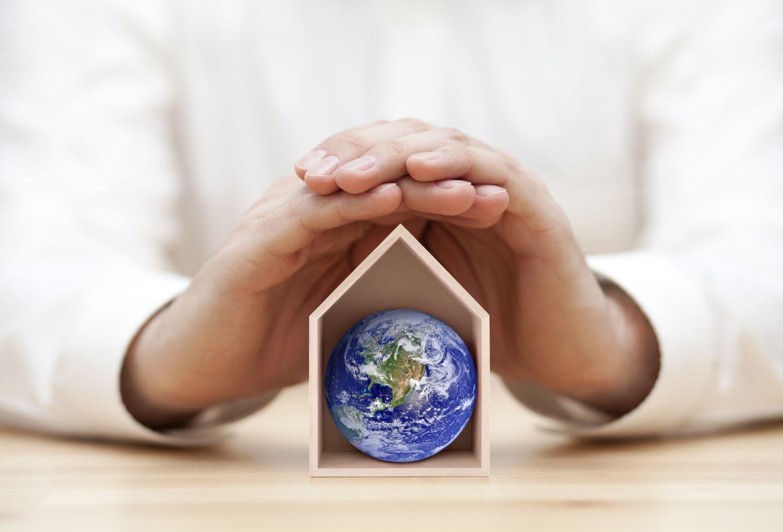 Schützende Hände über einem Haus, in dem die Erde zu sehen ist. Thema: Probleme der Energiewende