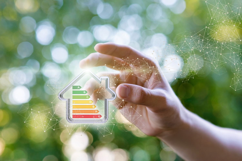 Hand hält virtuelles Haus mit Energieeffizienzklassen hoch. Thema: Energiekonzept