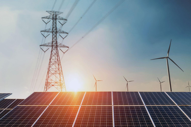 Freileitungsmast hinter einer Photovoltaik-Anlage in der untergehenden Sonne