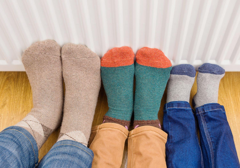 3 Paar Füße in bunten Socken lehnen an der Heizung, damit sie warm werden. Thema: Heizung umrüsten